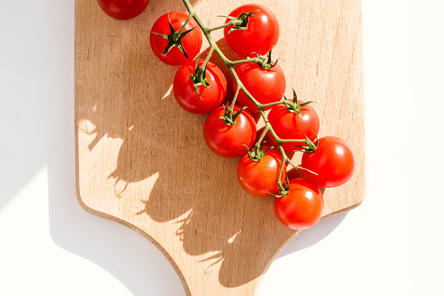 Fresh cherry tomatoes on wooden cutting board on white background