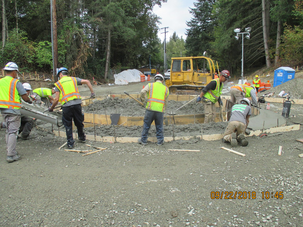 Workers pouring concrete on center island of Larch Way roundabout