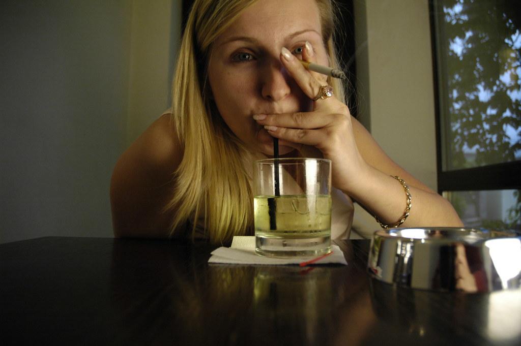 Donna bionda beve alcool e fuma