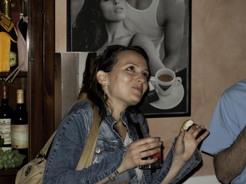 femme avec un verre d'alcool dans une main et un snack dans l'autre main