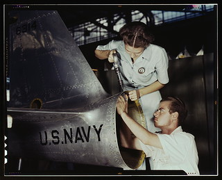 Mrs. Virginia Davis, a riveter in the assembly and repair department of the Naval air base, supervises Chas. Potter, a NYA trainee from Michigan, Corpus Christi, Texas. After eight weeks of training he will go into civil service. Should he be inducted or | by The Library of Congress