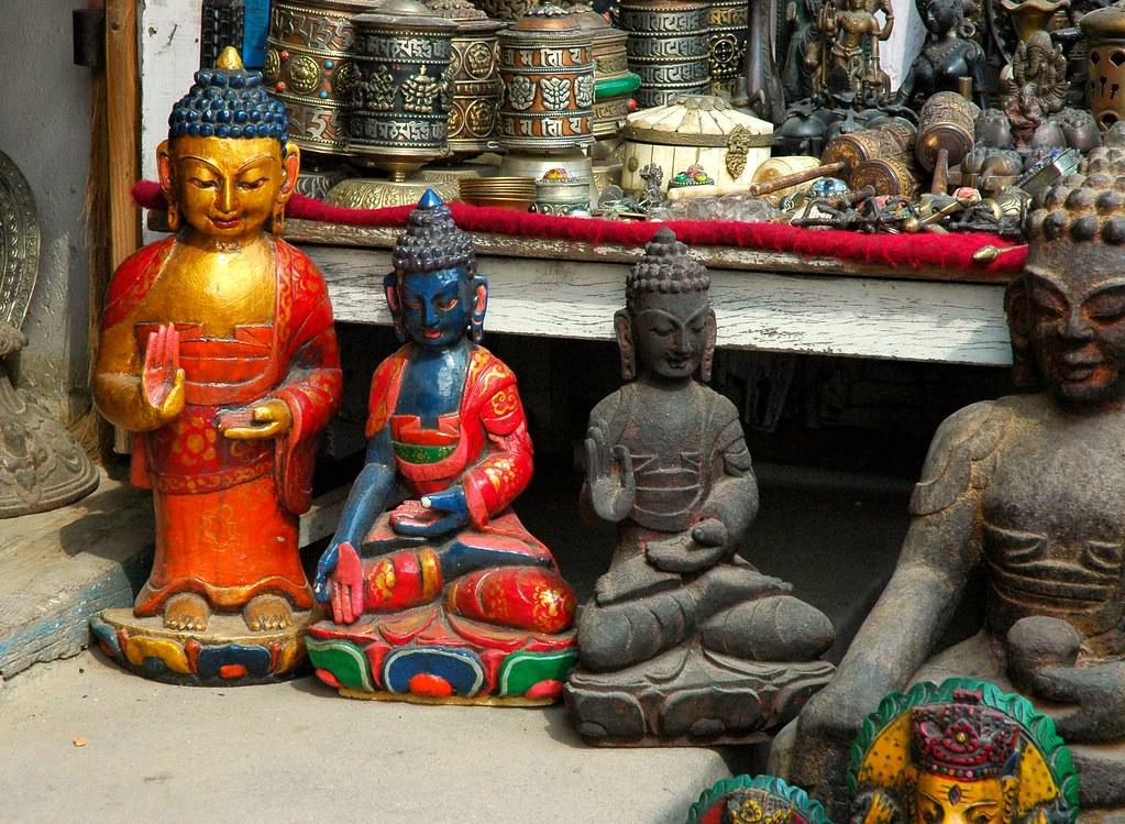 Four Buddhas in two mudras, prayer wheels - Tibetan Buddhist goods for sale, Boudha Stupa, Kathmandu, Nepal