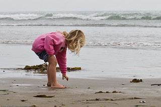 Kid plays in water and sand  on Morro Strand State Beach   by mikebaird