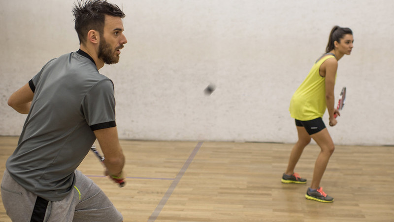 A man and a woman playing squash