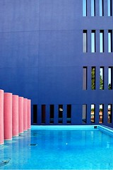 bright blue wall missing rectangles near pink cylinders