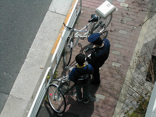 A kid getting ticketed for a traffic infraction on his bicycle.