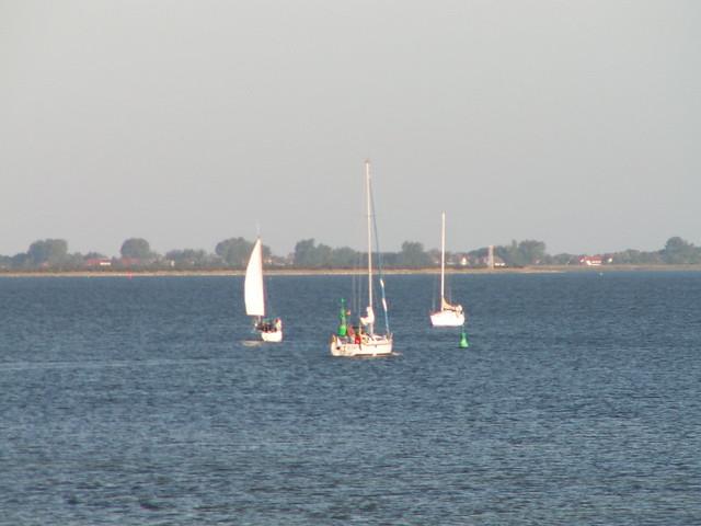 Mit zartem Zug richtet die Autofaehre  den Bug nach Schapprode auf der Insel Hiddensee in der Ostsee wo die Ausflugsschiffe anlegen und immer wieder steuern Yachten mit gehissten Segeln wie   Piratenschiffe im Kino vorbei  034