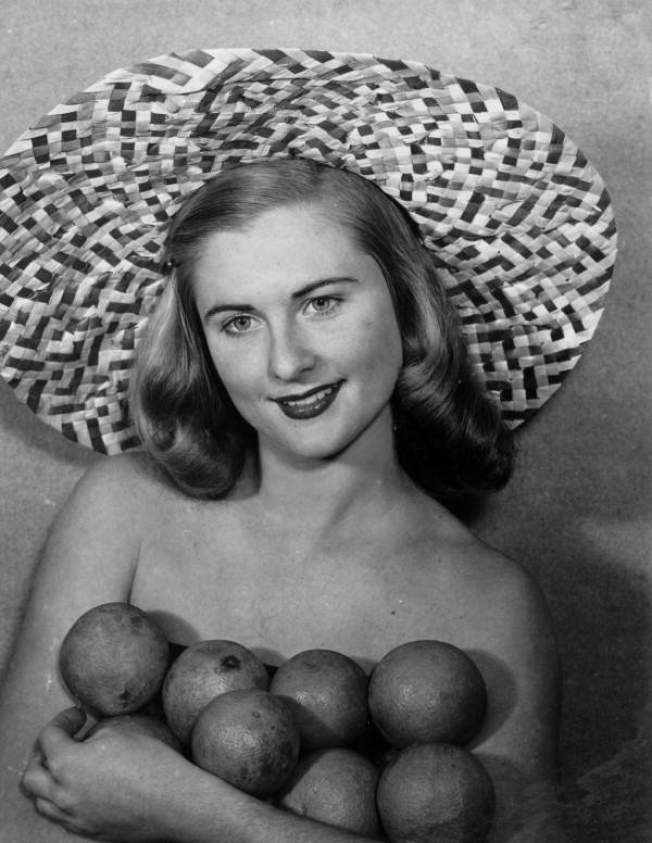 Evelyn Frankenberg wearing large straw hat displays Florida oranges - Lakeland