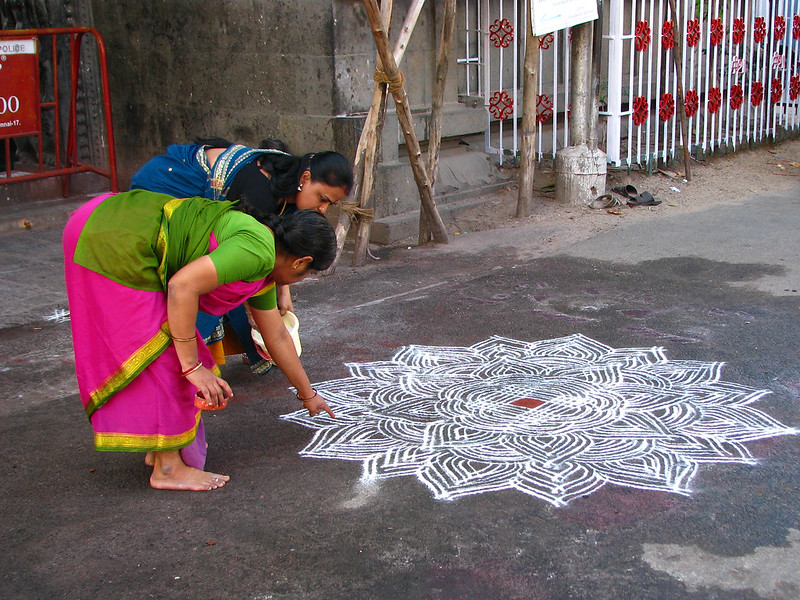 India - Sights & Culture - Women drawing an intricate kolam outside the Mylapore Temple