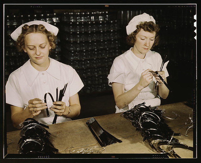 Two Navy wives, Eva Herzberg and Elve Burnham, entered war work after their husbands joined the service, Glenview, Ill. They assemble bands for blood transfusion bottles at Baxter Laboratories. Mrs. Burnham is the mother of two children  (LOC)