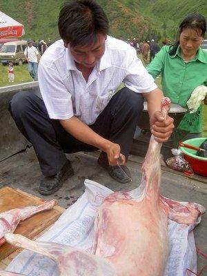 Jin Baoyuan cutting up a sheep