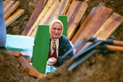 A woman by a grave in Srebrenica. | by The Advocacy Project