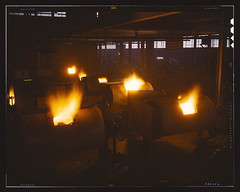 A battery of 1,000 and 2,000 pound furnaces roaring threats to the Axis. These are rotary, oil-fired melting furnaces at Aluminum Industries Inc. Destination of the finished aluminum products is kept secret  (LOC) | by The Library of Congress