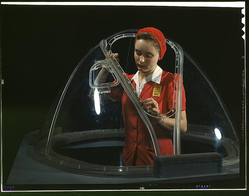 "This girl in a glass house is putting finishing touches on the bombardier nose section of a B-17F navy bomber, Long Beach, Calif. She's one of many capable women workers in the Douglas Aircraft Company plant. Better known as the ""Flying Fortress,"" the B-1 