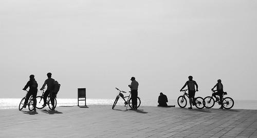 Chico, papelera y bicicletistas mirando al mar