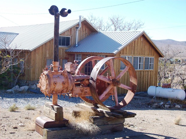 Old mining equipment on display in front of a yard at Darwin ghost town, CA (darwin15xy)