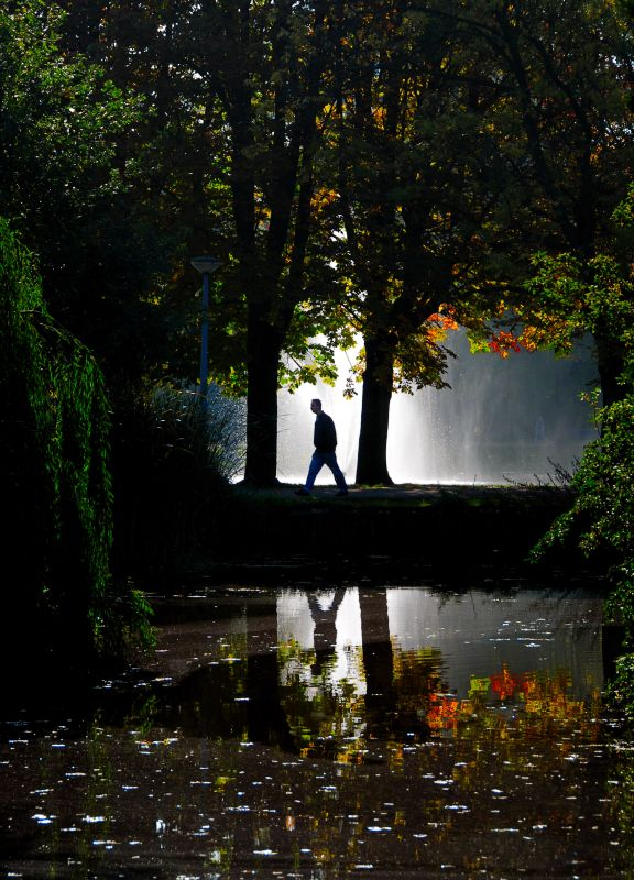 Lone figure caught in fountain's light! by James Rainsford