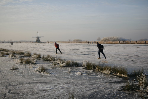 Ice skating in Friesland with mill   by Paul van Eijden™