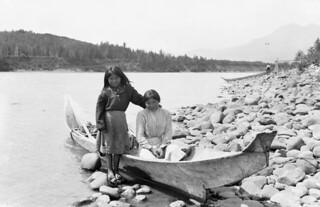 Two Gitxsan First Nation girls in a dugout cedar canoe by the Skeena River, Gitwangak, British Columbia / Deux jeunes filles de la Première Nation Gitxsan dans un canot de cèdre sur la rive du fleuve Skeena