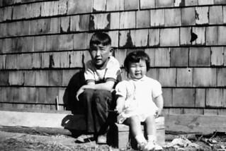 Eugene Hattori, first child of interned Japanese parents, and his sister Susan, Lethbridge, Alberta / Eugene Hattori, premier enfant né à Lethbridge, en Alberta, de parents japonais en camp d'internement. Il est photographié avec sa sœur Susan