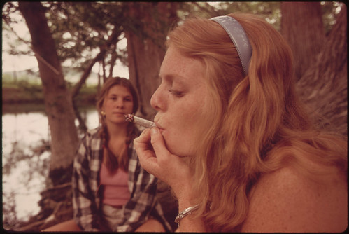 One Girl Smokes Pot While Her Friend Watches During an Outing in Cedar Woods near Leakey, Texas. | by The U.S. National Archives