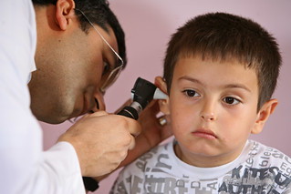 A child receives an ear exam as part of an overall health check up   by World Bank Photo Collection