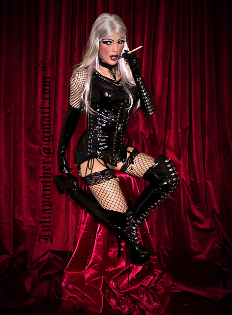 Erotic smoking in sexy latex corset, gloves, boots and fishnet
