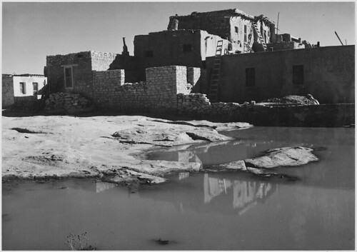 "Side view of adobe house with water in foreground,"" Acoma Pueblo [National Historic Landmark, New Mexico]."""