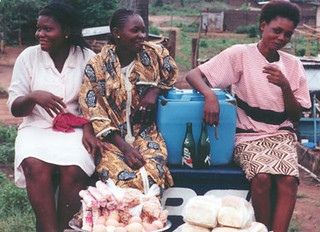 Three young women at a market stall in Lagos, Nigeria. | by The Advocacy Project