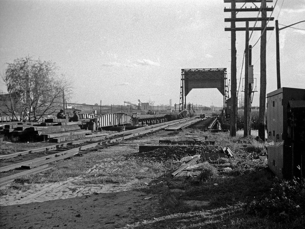 Abandoned Little Ferry New Jersey railroad tracks over the swampy Hackensack River. The World Trade Center is in the center distance.  November 1973
