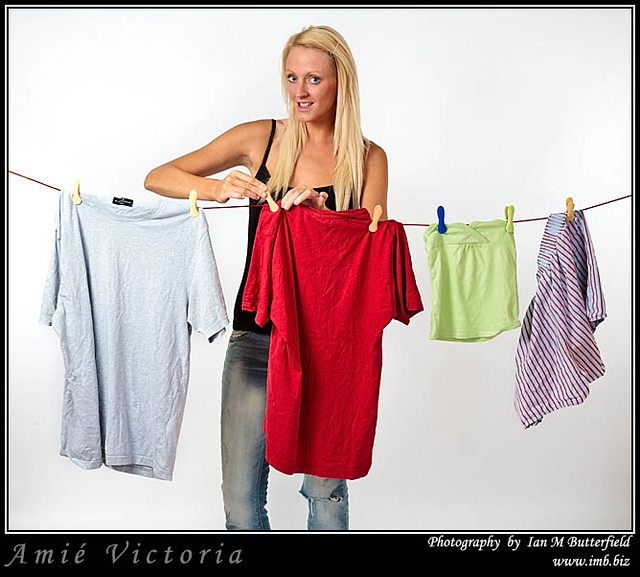 A young woman hangs out her laundry.