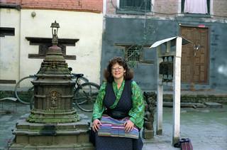 Linda Lane at a small Buddhist reliquary shrine wearing a Tibetan chuba, prayer wheels, Kathmandu, Nepal in 1993