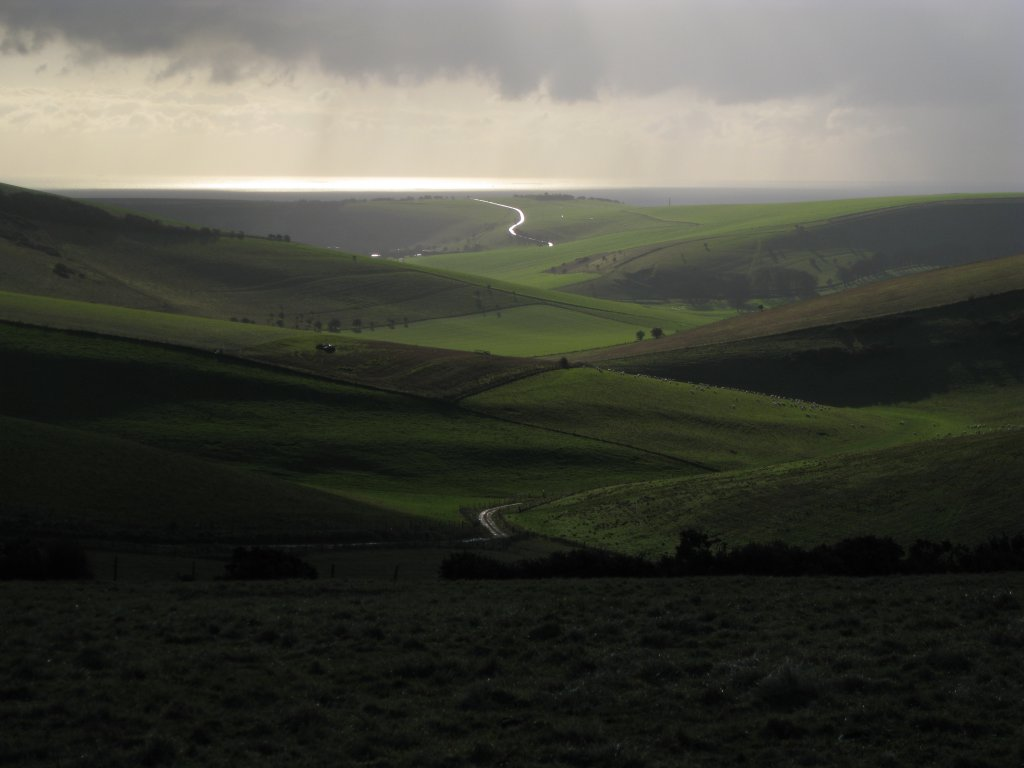 View towards Balsdean Farm and the Sea I love this view. It opens up upon reaching the South Downs Way coming from Kingston. Today it was just magic. A shower had passed just 10 minutes earlier, but then the green grass was shining in the backlight. Was almost blinded by the sun when taking this shot so unfortunately messed up the exposure a bit.