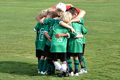 6 young children in green soccer uniforms huddled with their red shirted coach