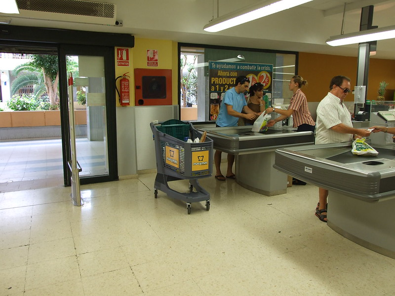 Couple at Check Out Counter with Plastic Shopping Cart.