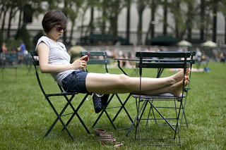 Girl with cell phone lounging in Bryant Park | by Andrew St. Clair