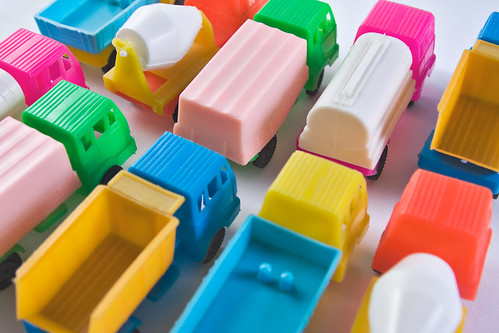 Colorful toy trucks parked together in rows | by Horia Varlan