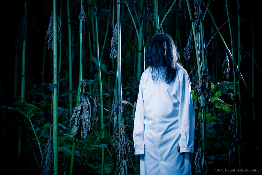 Strange creature with long hair in dark forest - a photo on
