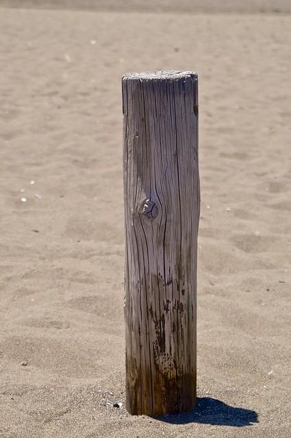 A pole in the sand on the beach