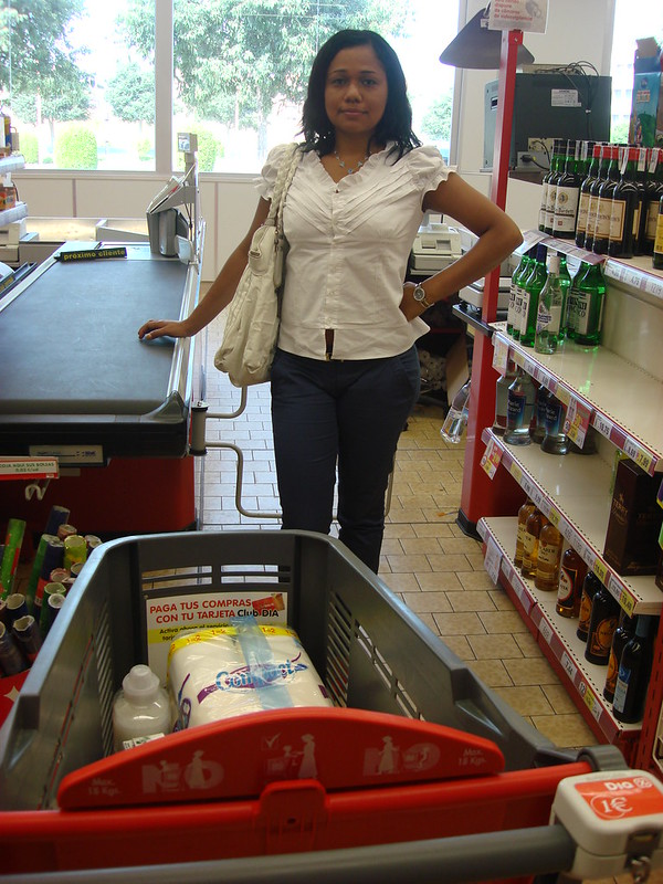 Woman at Check Out Counter with Plastic Shopping Cart.