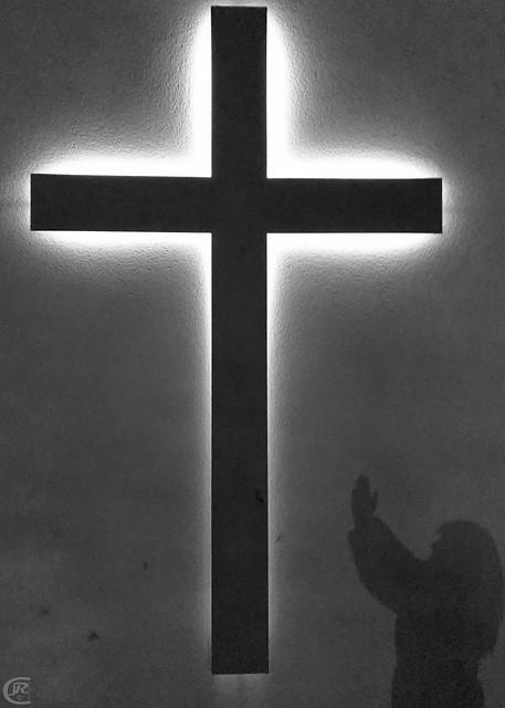 Silueta orando a la cruz