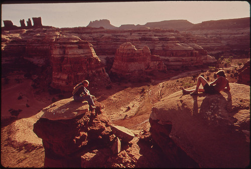 Hikers Terry Mcgaw and Glen Denny Enjoy a View of the Maze from the Top of a Ridge Separating Two Canyons. The Maze, a Wild and Rugged Region in the Heart of the Canyonlands, Has No Footpaths, and Hikers Enter by Means of Ropes Or Steps Cut in the Rocks, | by The U.S. National Archives