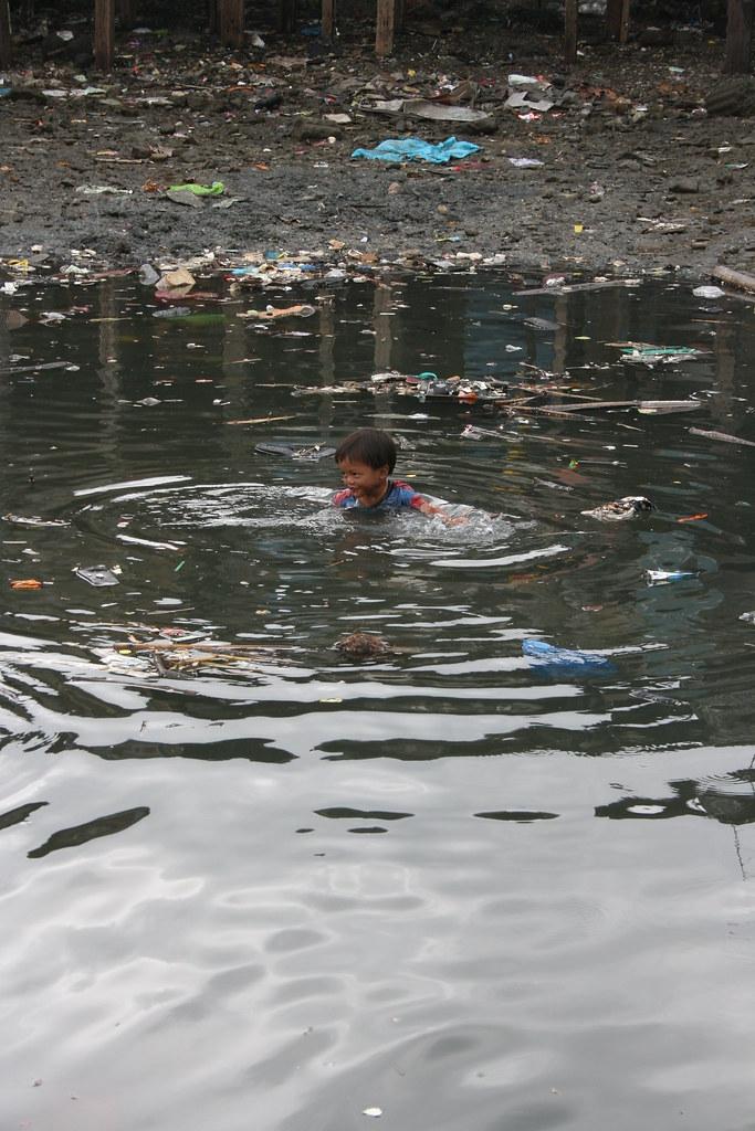 dirty water in slums of manila bay | A boy swimming in a mur