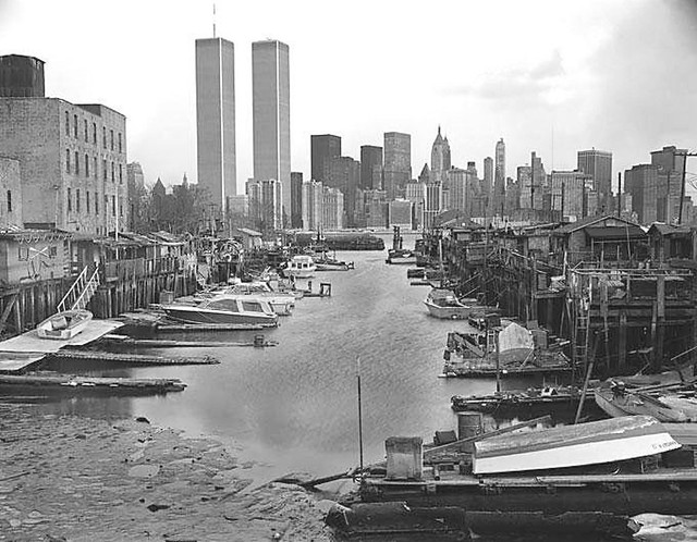 The ramshackle Greene Street Boat Club in Jersey City on the Morris Canal Small Basin graced by the World Trade Center across the Hudson River. 1982