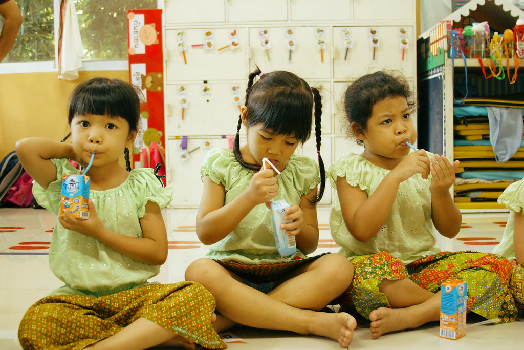 Three young girls drink milk from cartons