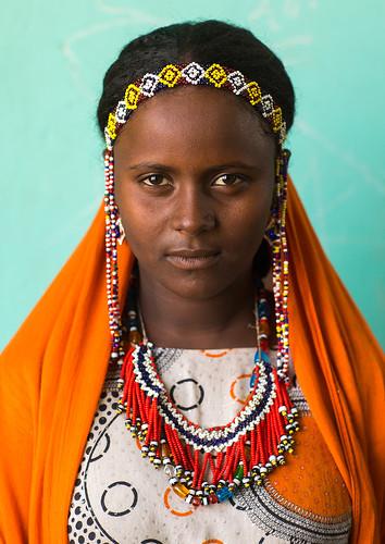 Chica de tribu lejana con gran collar y cabello trenzado