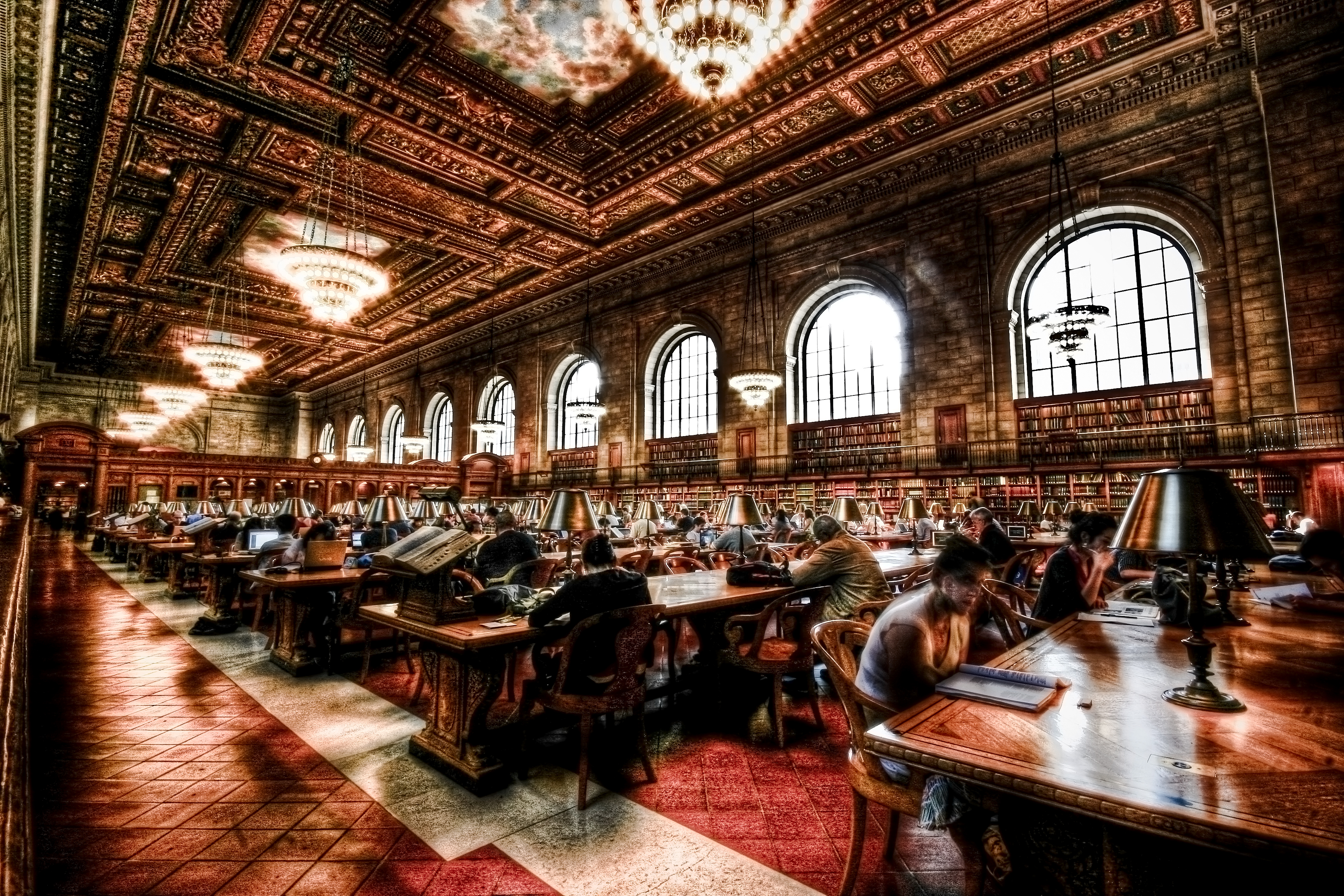People sitting at tables and working at the Rose Main Reading Room of the NYPL. A blur/color filter has been applied to the photo.