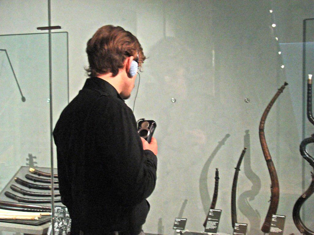 Visiteur devant la vitrine des cornets (musée de la musique)