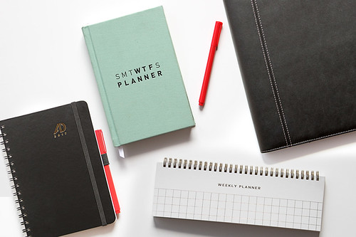 Four daily planners on a clean white desk | by yourbestdigs