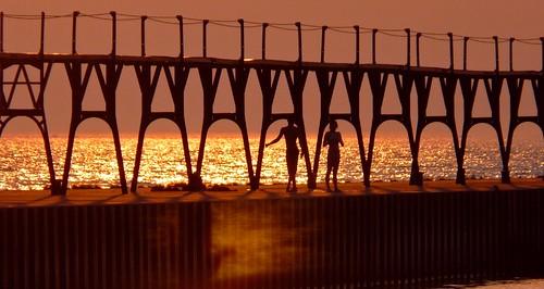 sunset sun lighthouse lake water metal pier jumping lads michigan lakemichigan panasonic catwalk manistee breakwater settingsun michiganlighthouse us31 scenicmichigan fz18 locallads jimflix llmsmimanistee
